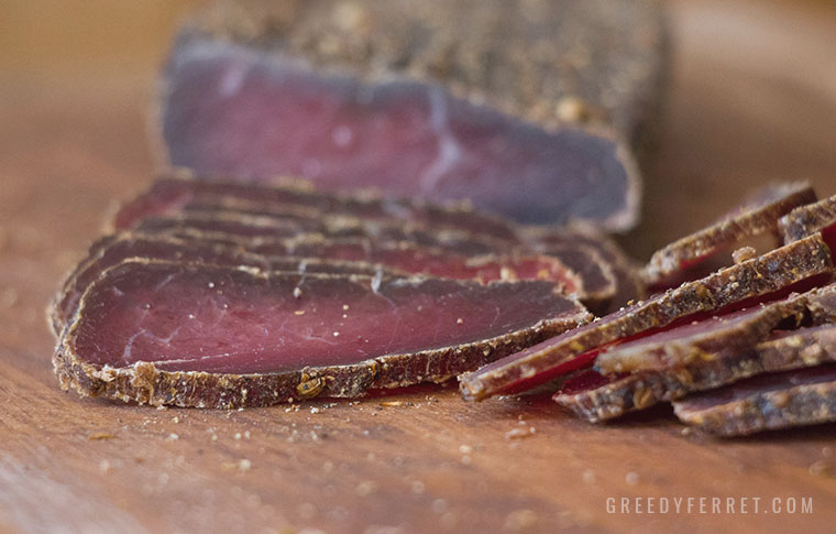 Wet biltong slices on a chopping board